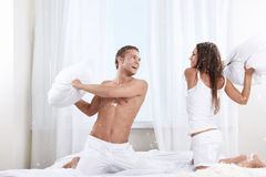 Fun. Young couple fighting pillows in the bedroom Stock Photo