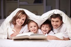 Fun. Parents with children under the blanket with a book Royalty Free Stock Image