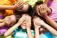 Fun. Portrait of happy preschoolers lying and closing eyes by hands Royalty Free Stock Photo