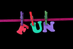 Fun. Letters forming the word fun hanged from a ribbon by different colour washing pegs stock photos