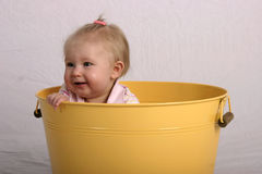 This is fun. Smiling baby inside a yellow bucket Royalty Free Stock Photo