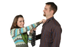 This is fun. Woman has a fun time getting her mans attention by tightning his neck tie knot Stock Photography