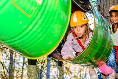 Fun in the Adventure Park. Little girl is going through the barrels in the adventure park stock photography