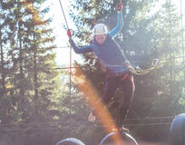 Fun in adventure park. Woung woman  hanging on tires in an adventure park in the forest Stock Photography