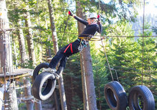 Fun in adventure park. Woung woman hanging on tires in an adventure park in the forest royalty free stock photos