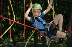 Fun in adventure park. Young boy climbing a rope way in an adventure park having fun Stock Photography