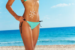 Fun applying sunscreen on beach body. Close up of tanned cute woman standing on the beach in blue striped swim wear and cute drawing of sun on her belly made of Stock Photography