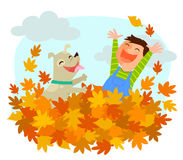 Fun of autumn. Boy and his dog playing in a pile of autumn leaves Stock Image