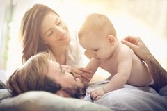 Fun with baby boy. Young happy parents with baby boy playing in bed. Space for copy stock photo