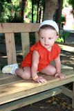 Fun baby girl in hat sitting on bench Royalty Free Stock Image