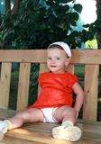 Fun baby girl sitting on bench Royalty Free Stock Images