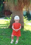 Fun baby girl standing near palm Stock Photography