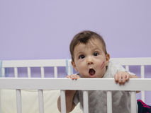 Fun baby with kiss mark on cradle. Stock Photos