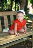 Fun baby sitting on bench Stock Photo