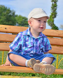 Fun baby sitting on bench. Little boy sits on a bench in a park Royalty Free Stock Photos