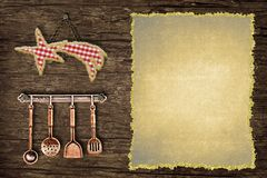 Fun background to write the Christmas menu. Star cloth tablecloth and old kitchen utensils hanging on a rustic wooden wall with blank parchment paper stock image