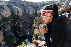 Fun backpacker woman. Portrait of an asian chinese backpacker smiling and drinking a mug of coffee while hiking and exploring on a tourist adventure in the Royalty Free Stock Images