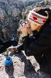 Fun backpacker woman. Portrait of an asian chinese backpacker smiling and drinking a mug of coffee while hiking and exploring on a tourist adventure in the Stock Image