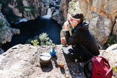 Fun backpacker woman. Portrait of an asian chinese backpacker smiling and drinking a mug of coffee while hiking and exploring on a tourist adventure in the Stock Images