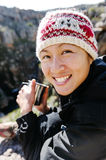 Fun backpacker woman. Portrait of an asian chinese backpacker smiling and drinking a mug of coffee while hiking and exploring on a tourist adventure in the Royalty Free Stock Photography