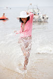 Fun at the beach. Beautiful brazilian girl splashing with water on the beach Stock Photos