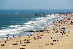Fun at the Beach. Wide shot of a crowded beach during the summer with pier and ship in the water Stock Images