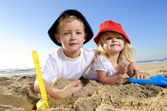 Fun at the beach. Gorgeous children,  brother and sister have fun digging in the sand at the beach Royalty Free Stock Photos