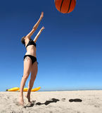 Fun on the beach. Girl playing with giant basketball on the beach Stock Photo
