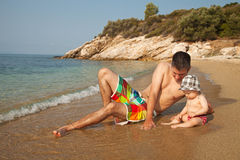Fun at the beach. Young men lying at the beach and playing with 9 months old baby Royalty Free Stock Image