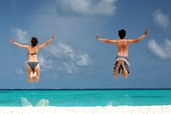Fun at the beach. Happy couple having fun on the beach jumping Royalty Free Stock Photo