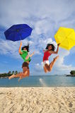 Fun at the Beach 45. Smiling faces at the beach jumping with umbrellas Royalty Free Stock Photography