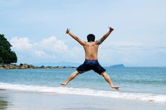 Man jumping on the beach stock images