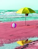 Fun beach concept with parasol. Shoes and inflatable ball in surrealistic colours Royalty Free Stock Image