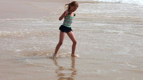 Fun with beach waves. Little girl playing with sea waves on the beach in sunny day stock video footage