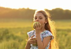 Fun beautiful kid girl with long hair joying and biting green ap Stock Photos