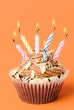 Fun Birthday Cake. Fun chocolate birthday cake with colored candles on orange background Royalty Free Stock Image