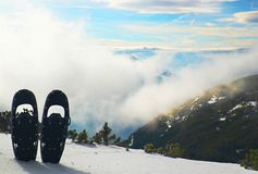 Fun black snowshoes in snow at mountain peak, nice sunny winter day Royalty Free Stock Images