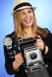 Fun blond female holding old camera. Photo of a beautiful young blond woman holding a vintage 4x6 film camera Stock Photography