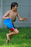 Fun with a blu bucket of water. A multi ethnic boy screams while running in the garden with a blu bucket of water Royalty Free Stock Photography