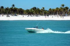 Fun in the boat. Motorboat speeding by the beach royalty free stock photos