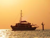 Fun Boat. On the sea at sunset sailing away royalty free stock photo