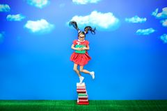 Fun with books. Happy little girl with a book in hand is jumping on a stack of books. Educational concept stock photography