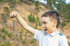 Fun boy with small fish Royalty Free Stock Images