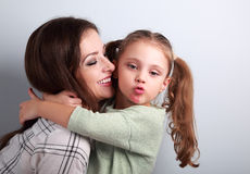 Fun bully kid girl showing kiss sign with mother lipstick kiss m Stock Image