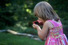 Fun with camera. A little girl playing with a digital camera Royalty Free Stock Photo