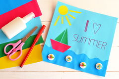 Fun card with text I love summer. Red pen, glue stick, scissors, colored paper. Card with paper ship, sun, sea, wooden buttons with fish pattern. Summer craft Stock Image