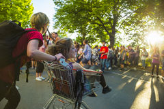 Fun at Carnival of Cultures - Karneval der Kulturen - in Berlin. Young woman pushing a shopping cart with a girlfriend sitting in it at sunset expressing joy and Stock Image