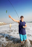 Fun Catch!. Active mature man with fishing pole, surf fishing, happy and smiling with the fish he successfully just caught on a great sunny day stock photos