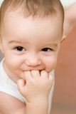 Fun caucasian baby with finger in his mouth Stock Image
