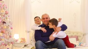 Fun cheerful father and children of twin brothers, on large bed in bright bedroom with Christmas tree.
